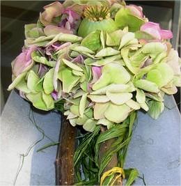 Creatief bloemschikken met restjes van hortensia en vruchten van papaver voor het maken van een tafelstuk
