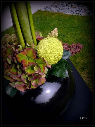 Afwerking bloemstuk met sierfruit en hortensia