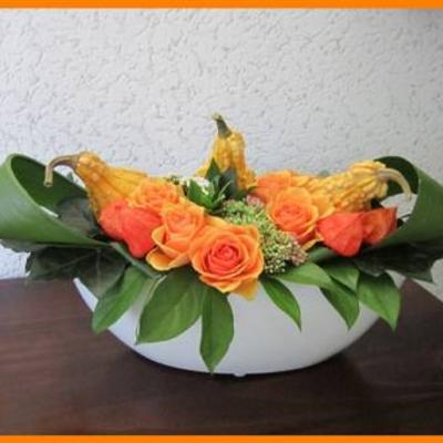 Bloemstuk met sierfruit en rozen.